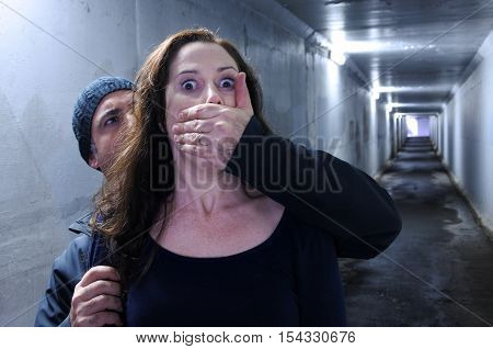 Man attacks a woman from behind in a tunnel. Violence against women concept. Real people copy space