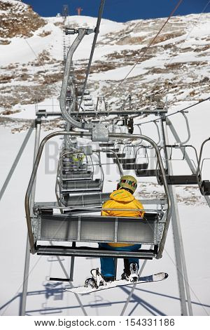 Young snowboarder in a yellow jacket elevating to the mountain top on a chairlift