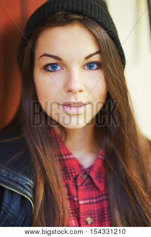 Portrait of young beautiful long-haired girl with blue lenses in a hat and checkered shirt close-up.