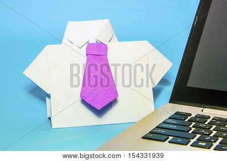 Shirt with a tie of origami paper near the laptop.