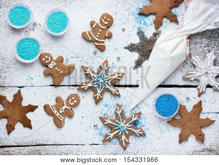Decorating gingerbread man and snowflake Christmas cookie background Christmas treats for kids cooking process concept