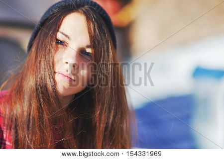 Wonderful portrait of a beautiful long-haired girl the sun shines in your face and wind in your hair close up on blurred background