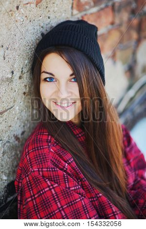 Trendy young woman in casual clothes posing against a brick wall.