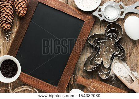 Christmas baking cookie background. Baking Christmas gingerbread man cookies. Dough ingredients and decorations on vintage planked wooden table top view copy space