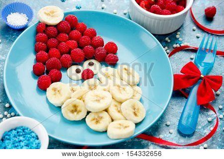Funny edible santa - banana raspberry and chocolate Santa face on plate. Christmas treats for kids