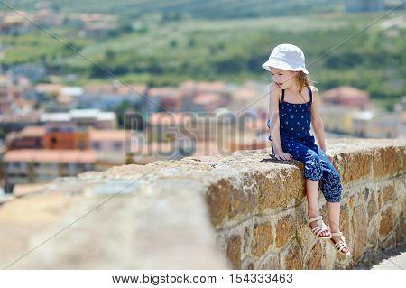 Little Girl Sitting On A Wall Enjoying A View