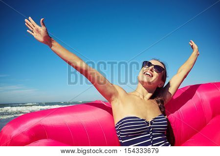 A pretty smiling female enjoying a hot sunny day on the beach sitting on the pink inflatable boat wearing brown-colored sunglasses and putting her hair in a braid, wearing striped bathing suit