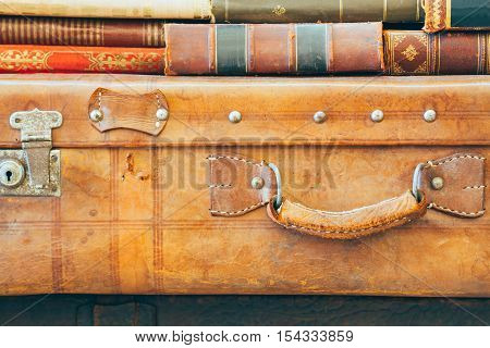 Antique suitcases with handle stacked with old books