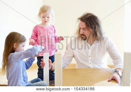 Father And His Two Daughters Assembling A Table