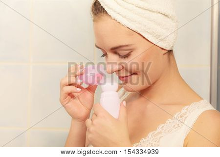 Woman holding stick deodorant in hands. Girl in bathroom towel on head with antiperspirant cosmetics. Daily skin care and hygiene.