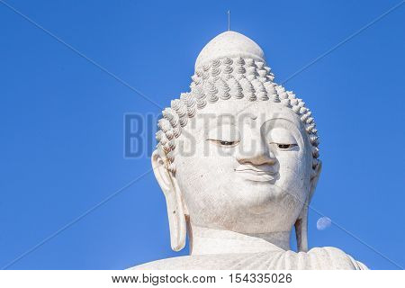 Close up of the Big Buddha head in the blue sky. Front view. Nakkerd hills in Ao Chalong, Phuket, Thailand.
