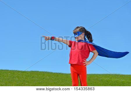 Superhero Girl Points Towards Dramatic Blue Sky