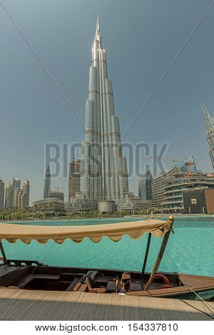 DUBAI, UAE - OCTOBER 11, 2016: A traditional wooden boat in the lake with Burj Khalifa in the background. The Burj Khalifa is the tallest structure in the world housing hotels and apartments