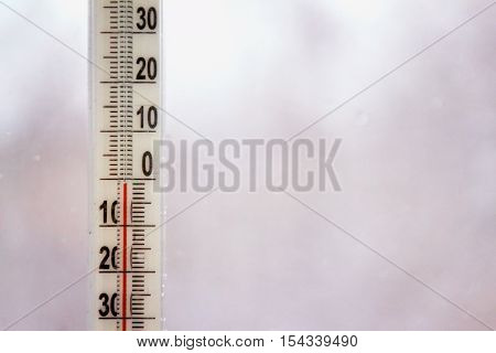 Outdoor thermometer with negative mark temperature on grey blurred background. Shallow depth of field. Focus on thermometer