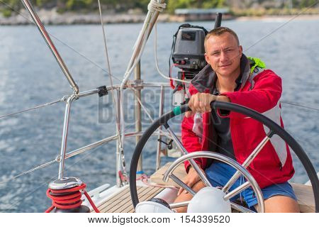 Man skipper steers boat sailing yacht on the sea.