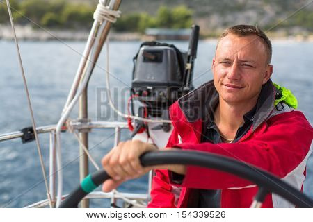 Man steers the controls of a sailing yacht boat.
