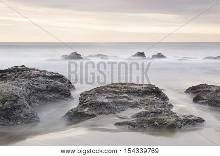 Serene seascape in Azkorri beach Biscay Basque Country Spain. Long exposure on a cloudy day.