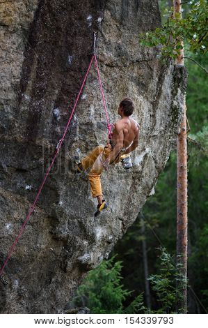 Rock climber having a rest while climbing, with harness and rope. Man abseiling from a steep rock.