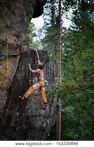 Man is climbing on rock. Success climbing, reaching the top Adrenalin, strength, ambition.