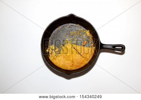 Half eaten pan of cornbread in a cast iron skillet isolated on white background