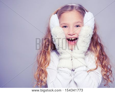 Girl in winter clothes. Happy surprised child. Studio shot