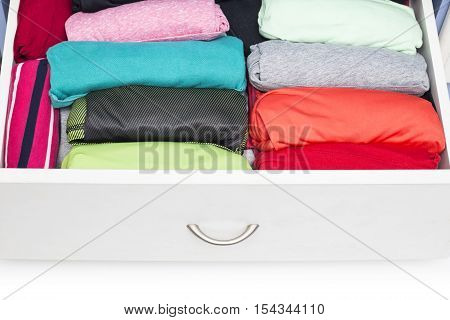 Clothing lying in the drawer in the wardrobe. on white background