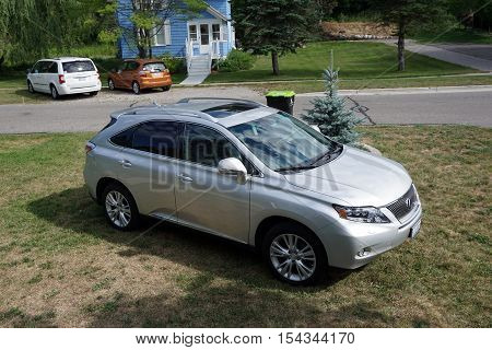 HARBOR SPRINGS, MICHIGAN / UNITED STATES - AUGUST 2, 2016: A Lexus RX-450h hybrid vehicle is parked in the front yard of a home in Harbor Springs.