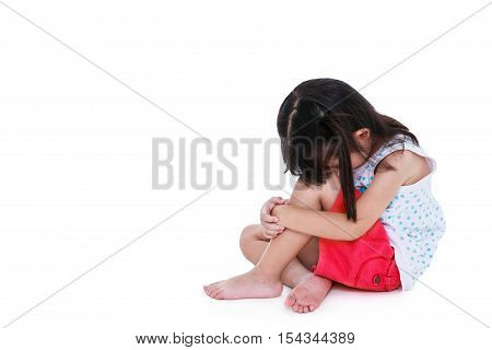 Sadness asian child barefoot sitting on floor with copy space. Isolated on white background. Negative human emotions. Conceptual about children who lack warmth and affection abandoned children.