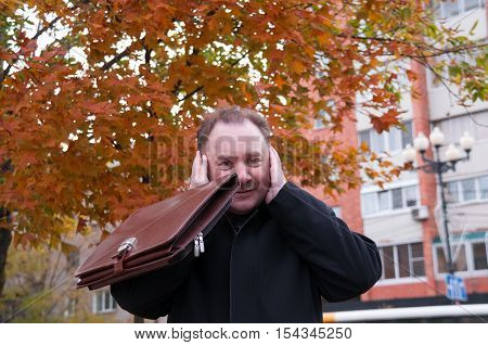 Man with a briefcase covered his ears against the backdrop of an orange maple