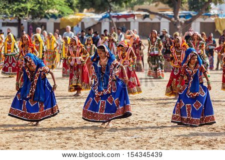 PUSHKAR, INDIA - NOVEMBER 21, 2012: Unidentified Rajasthani girls in traditional outfits dancing at annual camel fair  Pushkar Mela in Pushkar, Rajasthan, India