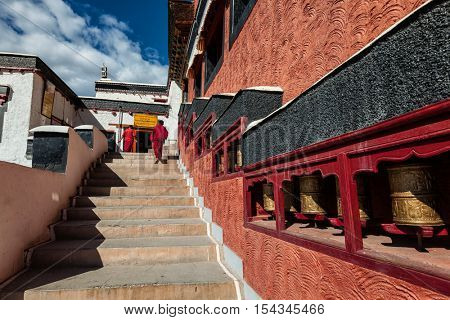 THIKSEY, INDIA - SEPTEMBER 13, 2012: Young Buddhist monks walkin on stairs along prayer wheels in Thiksey gompa Tibetan Buddhist monastery, Ladakh, India