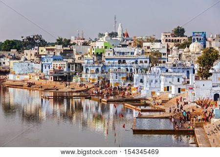 PUSHKAR, INDIA - NOVEMBER 20, 2012: Hindu devotees pilgrims bath in sacred Puskhar lake (Sagar) on ghats of Pushkar, Rajasthan. Pushkar is holy city for Hinduists and famous for many Hindu temples