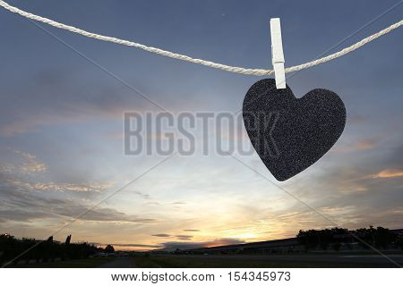 Black Heart hung on hemp rope on sunrise background and have copy space to manage the text you want.