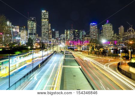 Multiple exposure image of skyscrapers and light trail of buses at bus station in downtown Brisbane, Australia at night