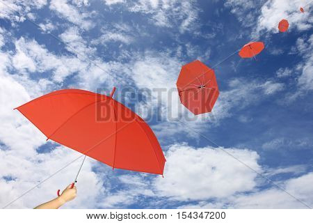 Red umbrella in hand on blue sky and cloud background umbrella blown by the wind in concept for management business idea.