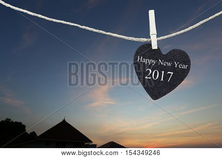 Black Heart hung on hemp rope on sunrise background and have Happy new year 2017 text.