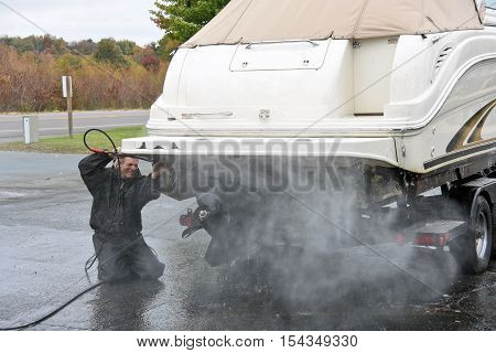 Caucasian man cleaning underside of power boat with pressure washer