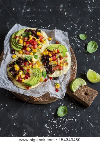 Spicy bean tostadas with corn salsa and avocado on a rustic cutting board on a dark background. Delicious vegetarian lunch or snack