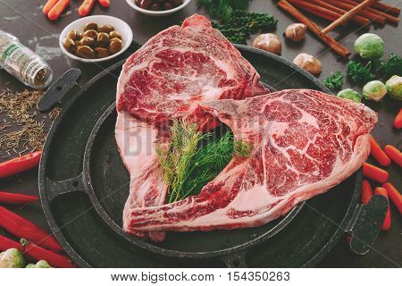 Raw double tomahawk beef steak with ingredients for grilling with a spice rub fresh rosemary on black table.