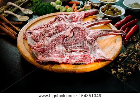 Raw triple tomahawk beef steak. with ingredients for grilling with a spice rub fresh rosemary on black table.