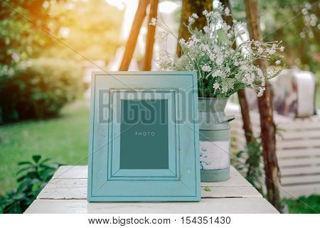 vintage blank frame with flowerpot on table in wedding day