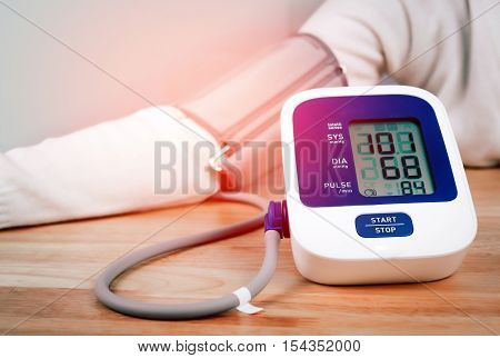 digital blood pressure monitor with patient on wooden table
