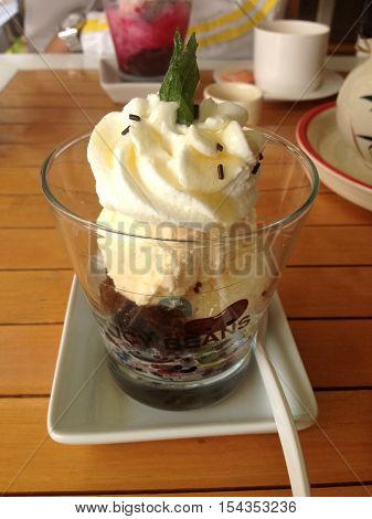 Cold vanilla icecream with red bean on wooden table