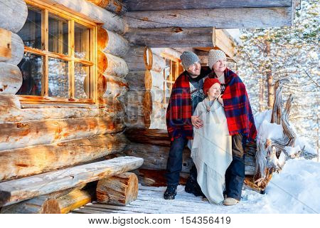 Family with child outdoors on beautiful winter day in front of log cabin vacation house