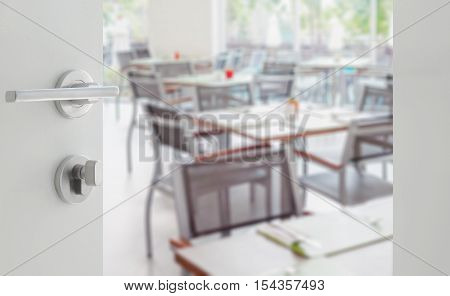 Opened White Door To Wooden Table And Chair In A Restaurant