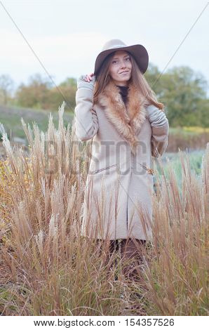 Woman in beige fur coat and felt fedora hat in the dry autumn field