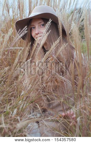 Woman in beige fur coat and felt fedora hat in high grass dry autumn field