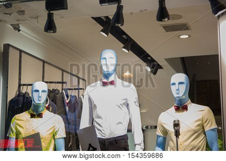 There are three blue mannequins in the bright lit showcase. All mannequins are dressed in men's shirt and bow tie.