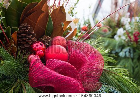 Big red bow in the middle of a fresh pine Christmas arrangement