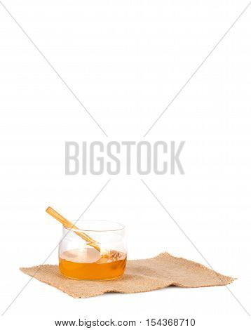 Fresh Liquid Honey In A Glass Jar And A Wooden Spoon